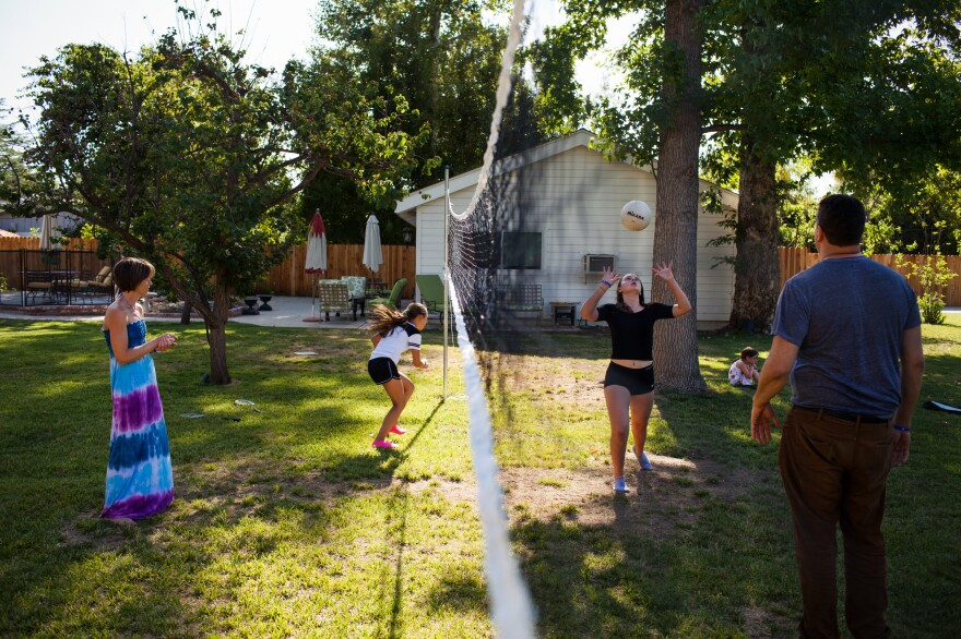 The Glasser family plays volleyball in their backyard.