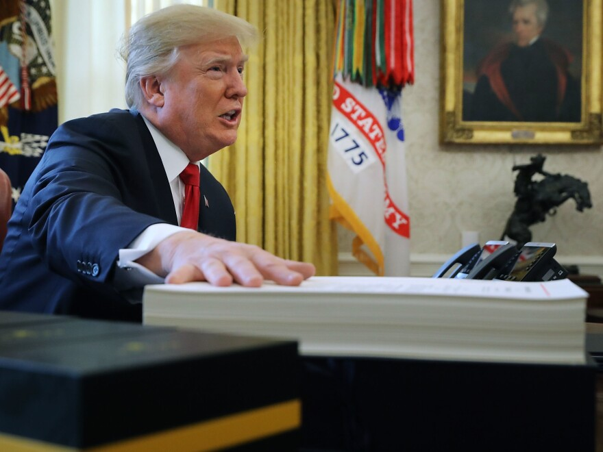 Analysts say real estate tax breaks allowed President Trump to personally avoid high taxes. Above, Trump prepares to sign tax legislation into law in the Oval Office on Dec. 22, 2017.