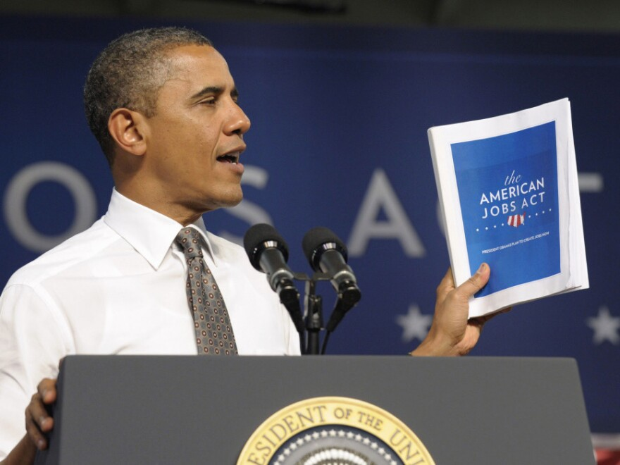 """<p>President Obama holds up a copy of his jobs bill as he speaks at Eastfield College in Mesquite, Texas. Obama is challenging a divided Congress to unite behind the bill or get ready to be run """"out of town"""" by angry voters. </p>"""
