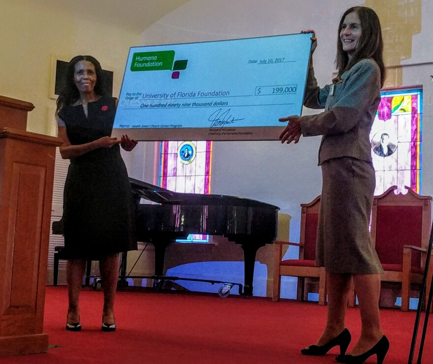UF Health's Dr. Carolyn Tucker (left) and Humana's Deborah Galloway holding Health-Smart's grant check Monday.