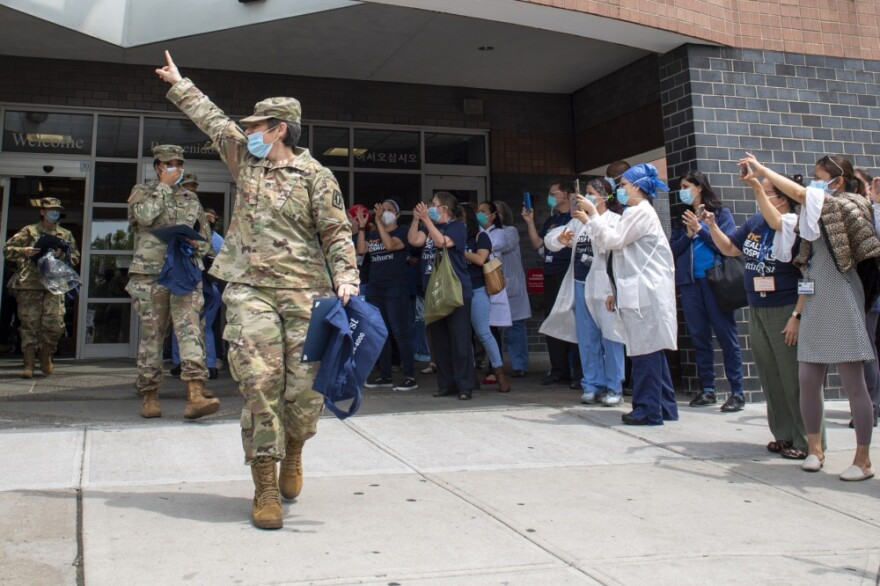 Service member walking out of a hospital to applause from doctors and nurses in scrubs.
