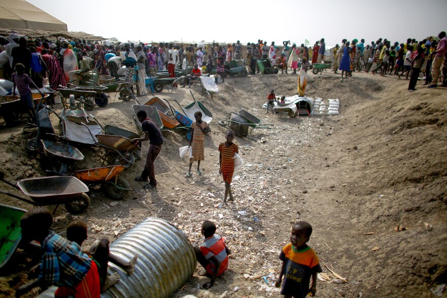 People stand in line for food rations while children play in a ditch at the camp.