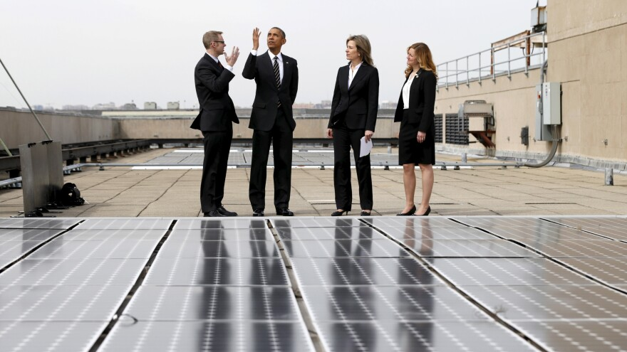 President Obama, seen here inspecting solar panels on the roof of the Department of Energy, has submitted a U.S. pledge to reduce greenhouse gases.