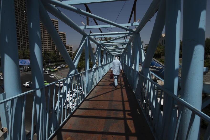 A woman walks on a pedestrian bridge in Tehran.