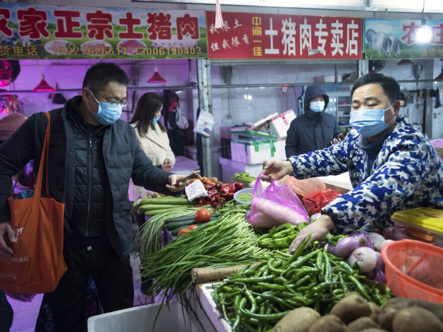 In a photo released by China's Xinhua News Agency, people wearing masks shop for vegetables at a market in Wuhan in central China's Hubei Province, on Thursday.