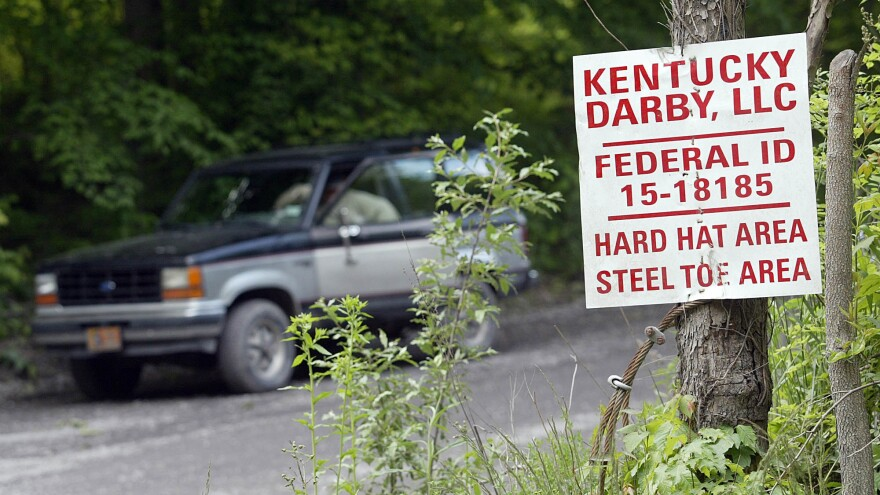 A guard sits in his truck at the entrance to the Darby Coal Mine in Holmes Mill, Kentucky, on May 20, 2006 - the day an explosion in the mine killed five miners. The owners of the mine later failed to pay nearly $3 million in penalties for mine safety violations at Darby and other mines.