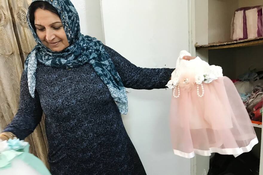 Caregiver Fajriya Khaled holds new clothes for the children for an upcoming holiday.