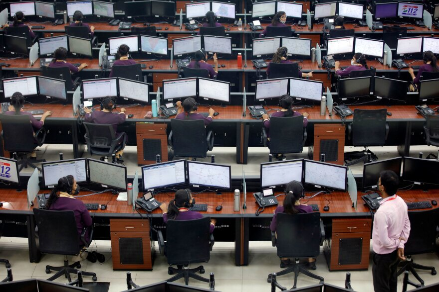 Employees wearing protective masks work in a call center run by Uttar Pradesh state police in April during a lockdown to slow the spread of COVID-19 in Lucknow, India.