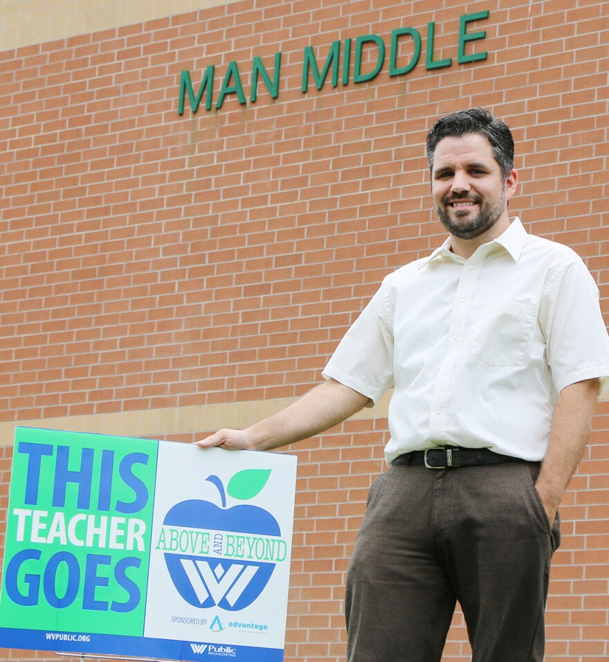 Garron Staten with his Above and Beyond yard sign in front of Man Middle School.