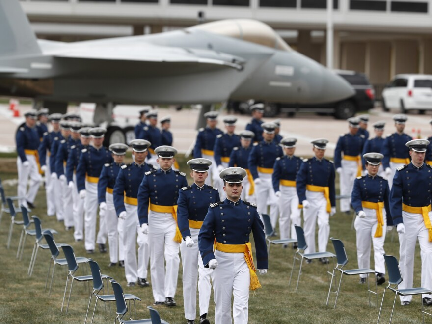 Cadets practicing social distancing march to their seats to start the graduation ceremony at the U.S. Air Force Academy.