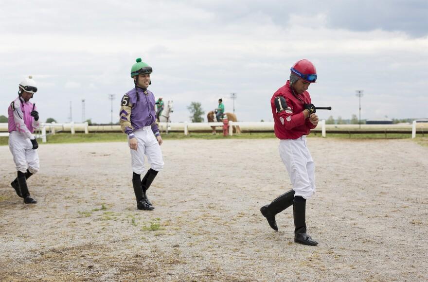 Jockeys head toward their horses after changing between races.