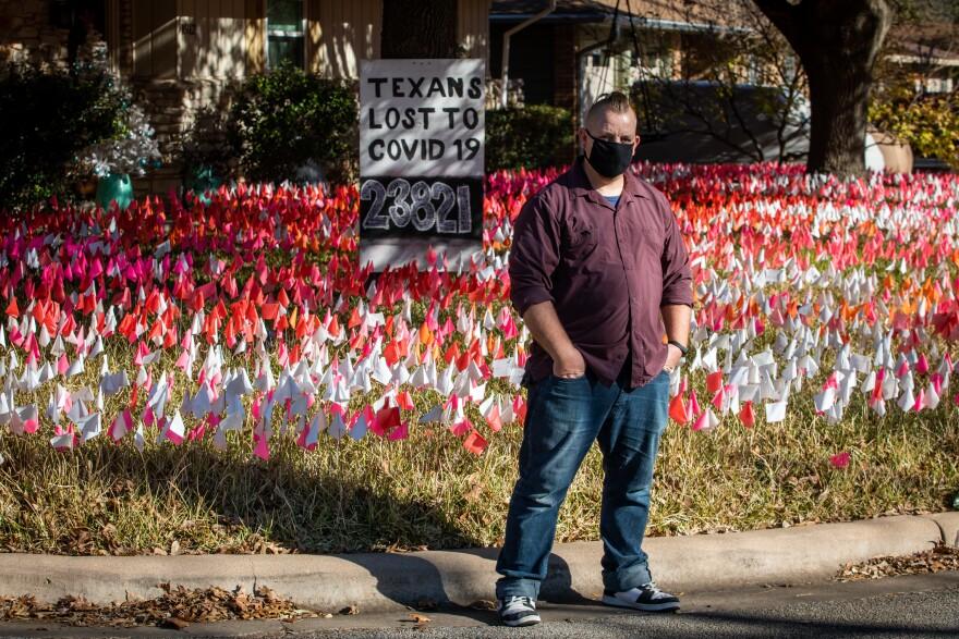 Shane Reilly frente a su casa en Brentwood, donde ha plantado banderillas por cada tejano muerto por COVID-19.
