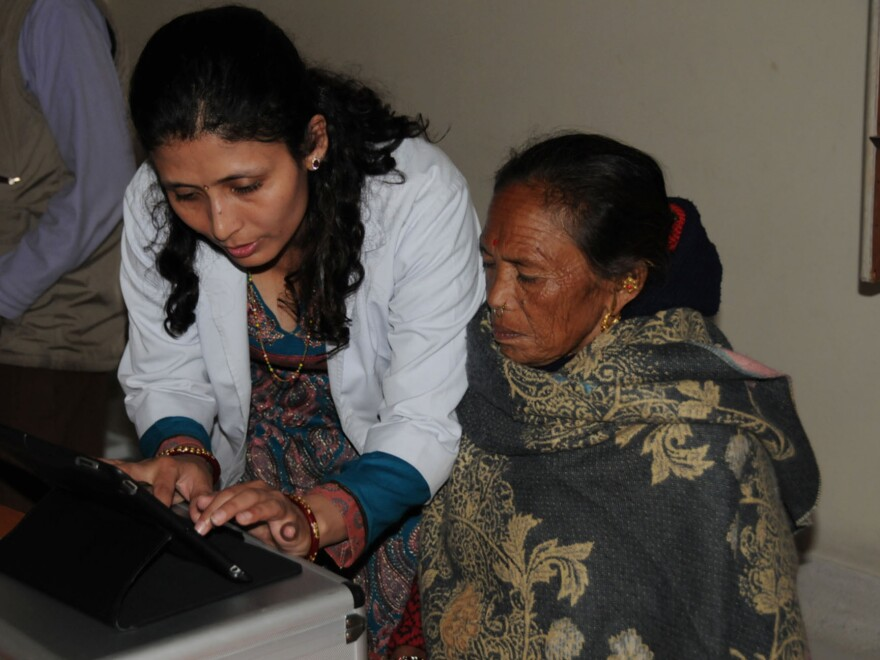 A researcher shows a woman in Nepal how to use a visual field test on an iPad. It's used to diagnose glaucoma.