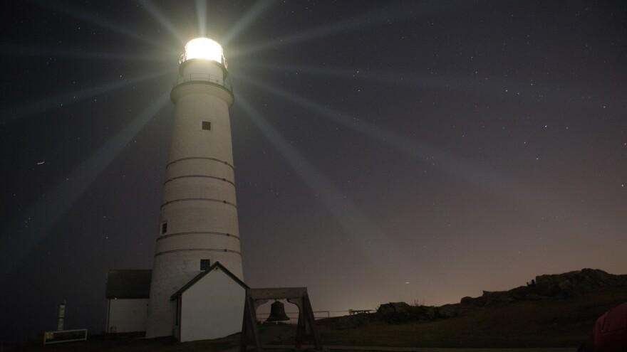 Boston Light, America's first lighthouse, beams light across the night sky.