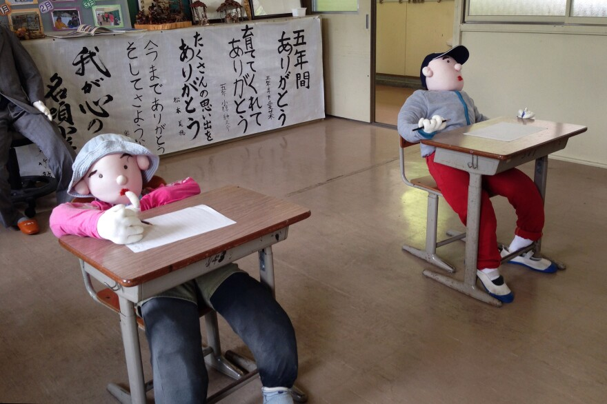 The child figures represent the last two students who were there before the school was closed. The school is now open to show Ayano's work.