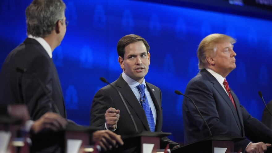 Marco Rubio (center) was able to stand out even while being targeted by Jeb Bush (left), someone once described as a mentor. Donald Trump looks on.