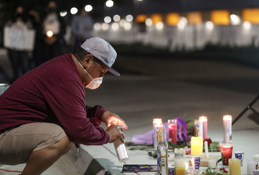 "A man sets a candle outside the Otay Mesa Detention Center during a ""Vigil for Carlos"" on May 9 in San Diego. The vigil was held to commemorate Carlos Ernesto Escobar Mejia, who died of COVID-19-related symptoms at the detention center."