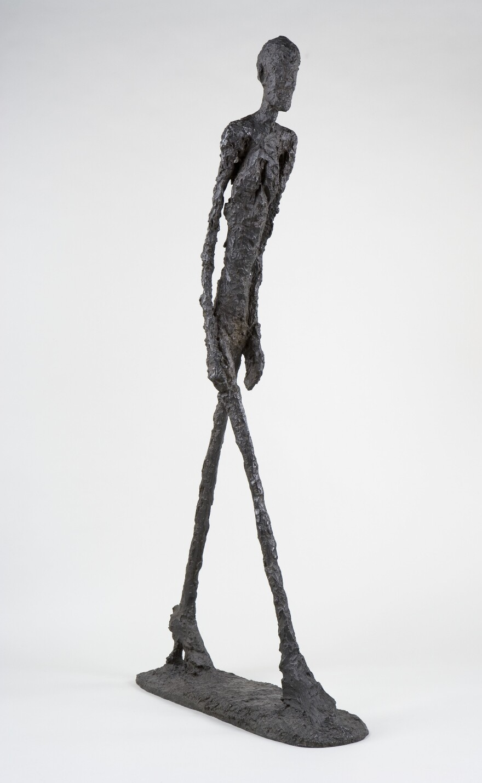Giacometti's impossibly thin bronze bodies stride like shadows. Above, his 1960 sculpture <em>Walking Man I </em>(<em>Homme qui marche I</em>).