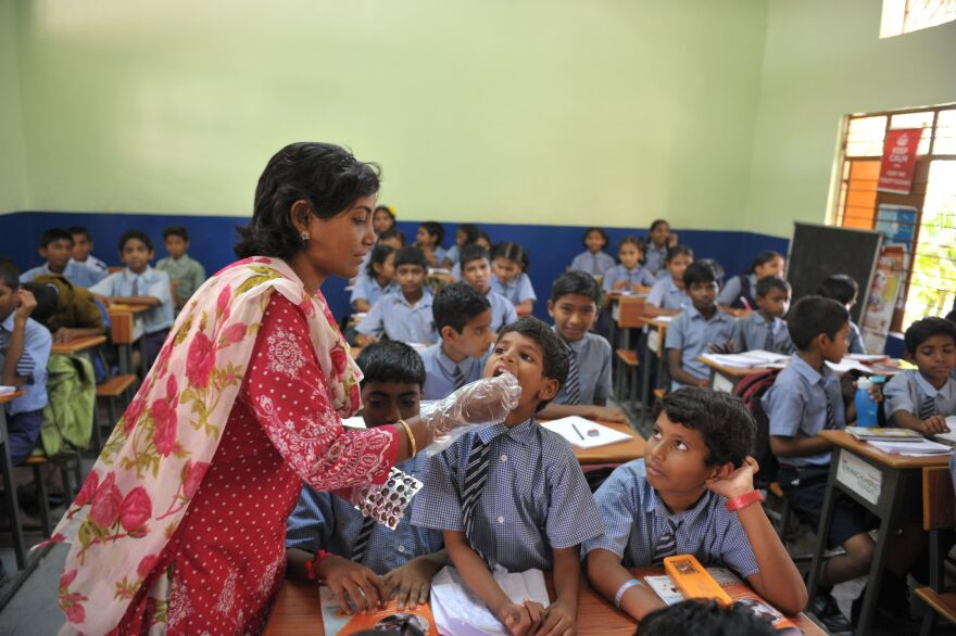 A teacher gives a deworming tablet to a student during National Deworming Day at a high school in Hyderabad, India, in 2017.