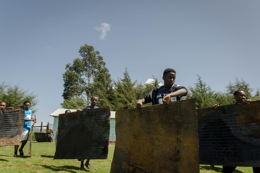 The group carries iron sheets that will be used as siding on classrooms they helped build during a two-week trip to Kenya.