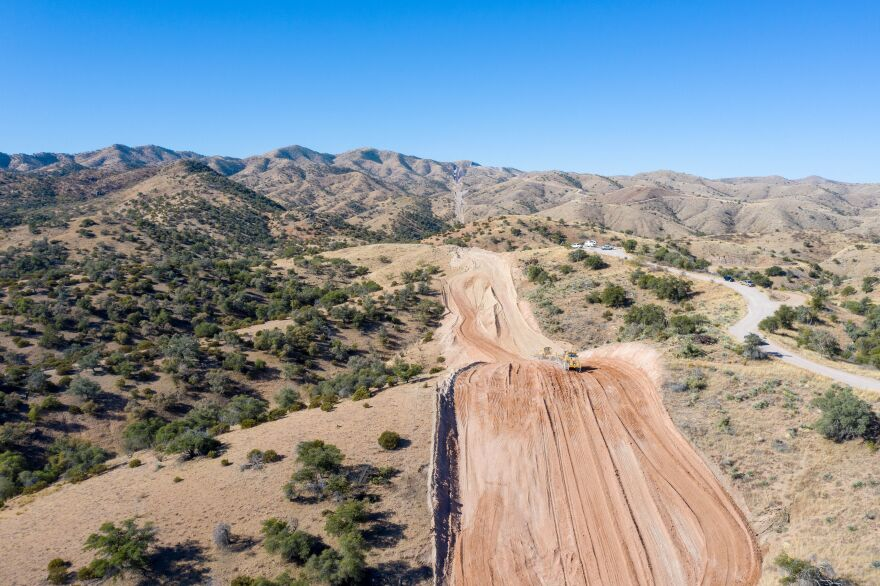 Heavy equipment is clearing a path for the border wall next to  Coronado National Forest in Southern Arizona. Mexico is on the left.