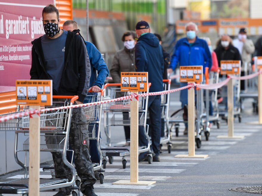 Customers wearing face masks line up in front of a DIY store in Innsbruck, Austria. The store reopened on Tuesday, after shuttering to limit the spread of the new coronavirus.