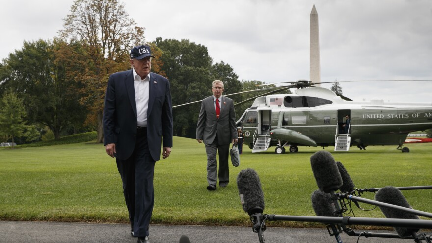 President Trump walks with Coast Guard Rear Adm. Peter Brown to speak to the media on return to the White House from Camp David on Sept. 1.