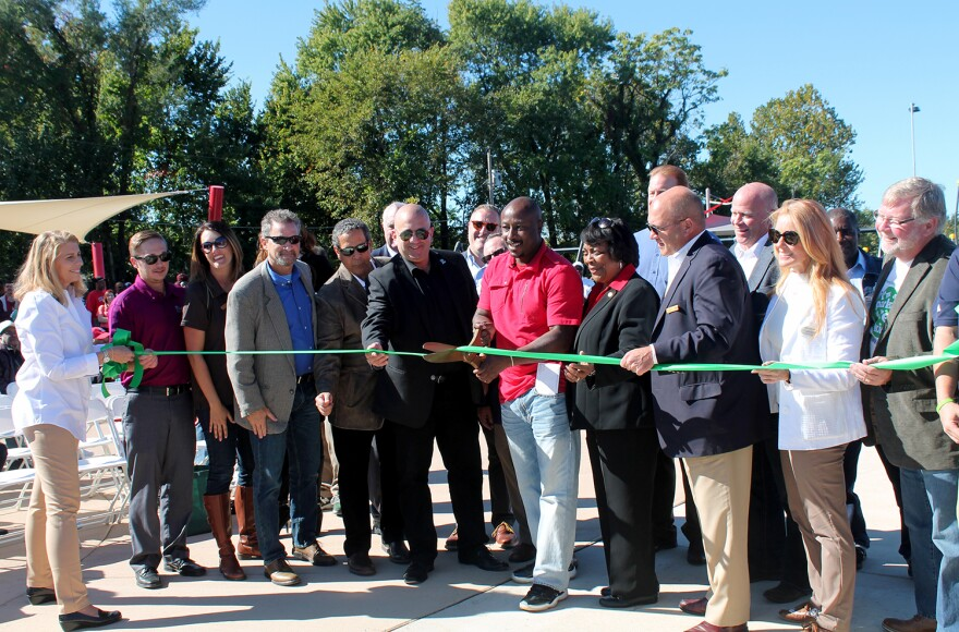 Wellston Mayor Nathaniel Griffin and Hazel Erby, center, cut the ribbon to celebrate the opening of Trojan Park as representatives from Great Rivers Greenway, the National Recreation and Park Association, donors and vendors surround them on Oct. 8, 2016.