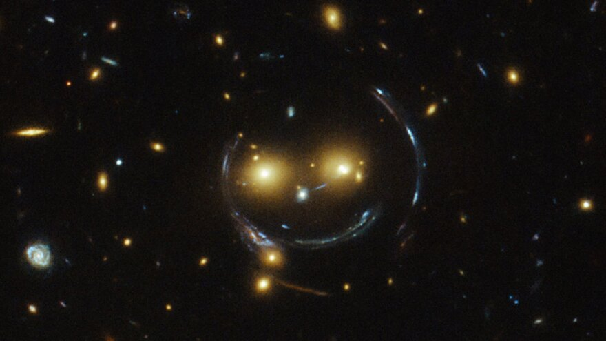 An image taken with the NASA/ESA Hubble Space Telescope of the galaxy cluster SDSS J1038+4849 shows that it seems to be smiling. The space agency says it's the result of a symmetrical alignment of the galaxy cluster and the telescope — along with a powerful gravity field that can bend light.