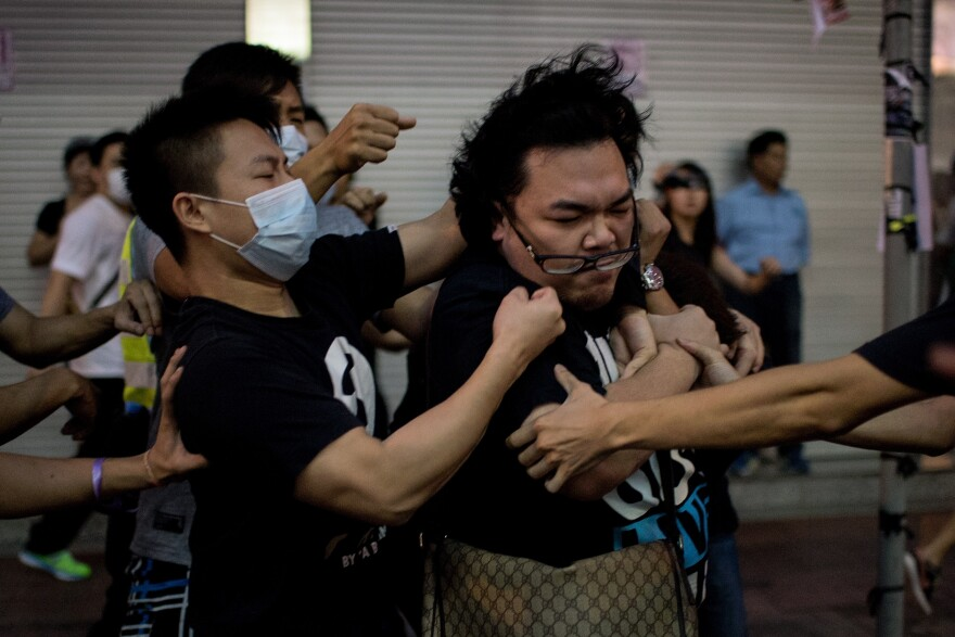 A group of men in masks rough up a man who tried to stop them from removing barricades from a pro-democracy protest area in the Causeway Bay district of Hong Kong on Friday.