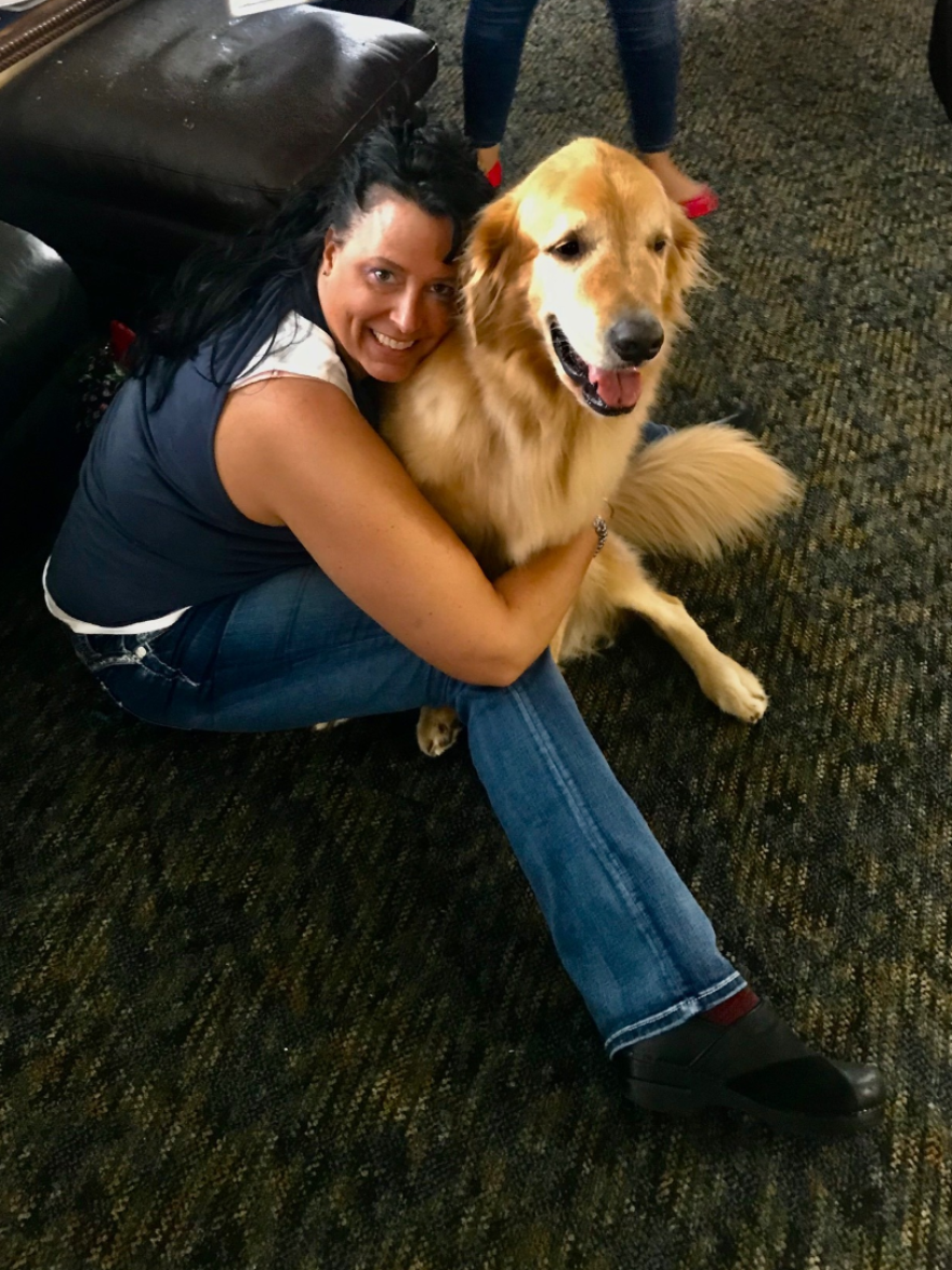 Veteran Kathleen Stadler sits with Hero, the therapy dog at the nonprofit Veterans Alternative's team house.