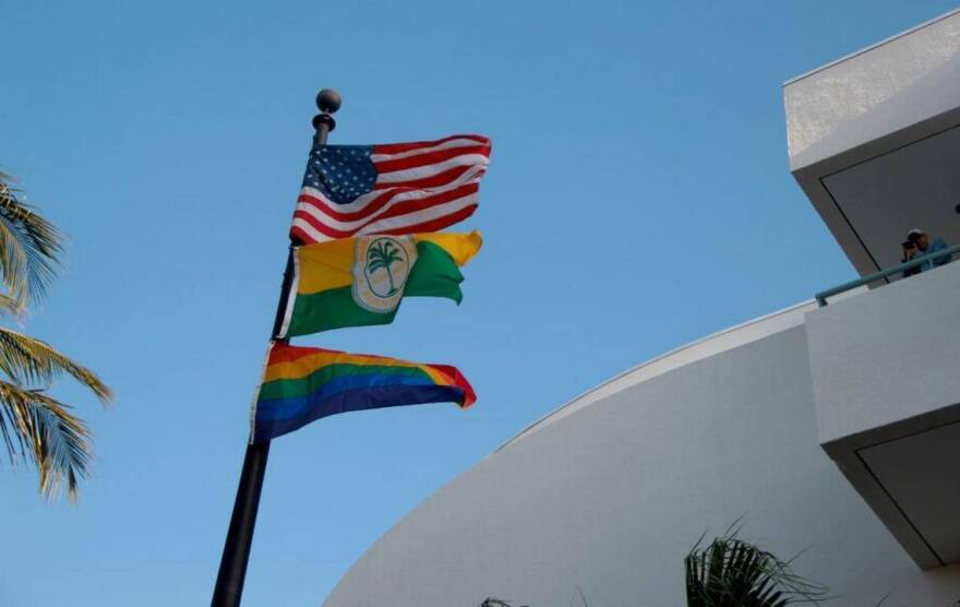 The American flag, the City of Miami Beach flag and the rainbow flag fly at Miami Beach City Hall during Gay Pride Week.