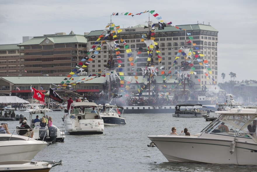 A pirate ship adorned with brightly colored flags is surrounded by smaller yachts on the river.