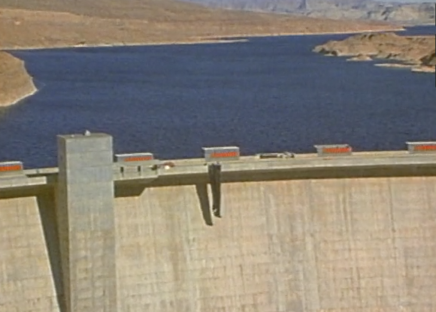 Close up photo of the top portion of a massive dam, with a black tarp draped over the edge.