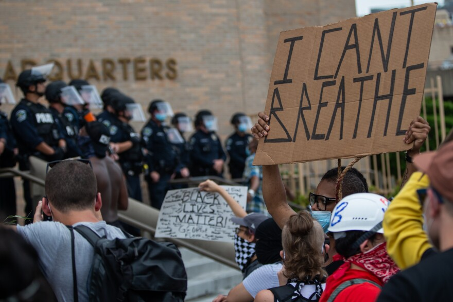 Austin Police officers stand outside APD headquarters during protests against police killings and systemic racism.