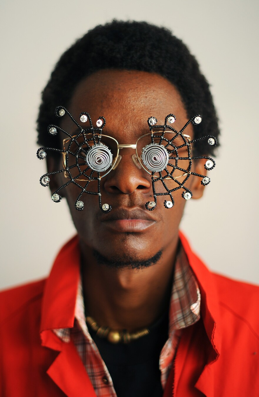 "Kenyan artist Cyrus Kabiru poses with an artwork resembling sunglasses on February 1, 2012 in Nairobi. Kabiru has created a range of artworks called ""c-stunners"" that resemble sunglasses but have been made with objects found on the street on his way to his studio."