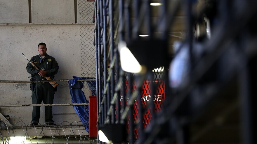 An armed California Department of Corrections and Rehabilitation officer stands guard at San Quentin State Prison's death row.