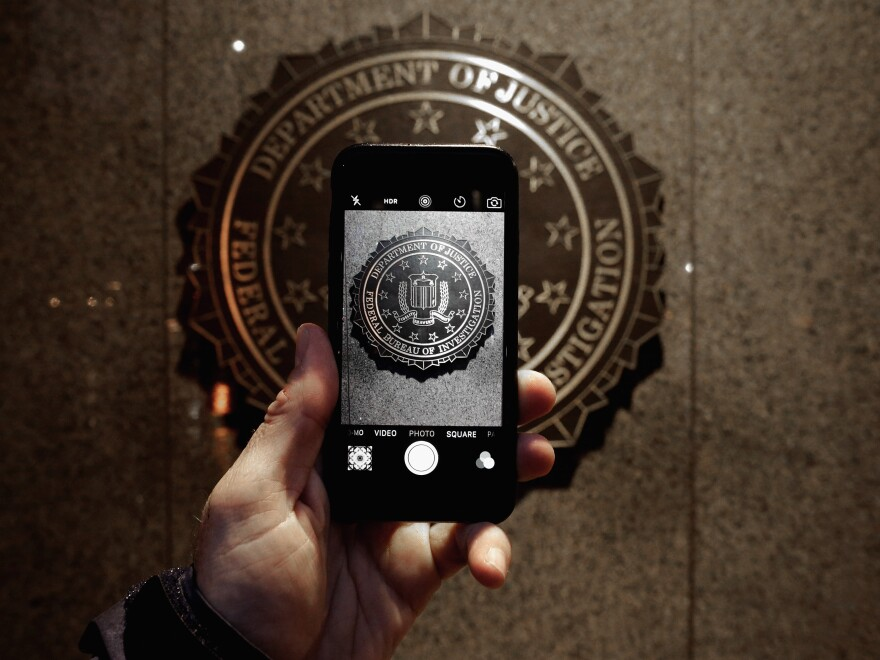 The official FBI seal is seen on an iPhone camera screen outside the agency's headquarters. With help from a third party, the FBI managed to unlock the iPhone used by one of San Bernardino shooters.
