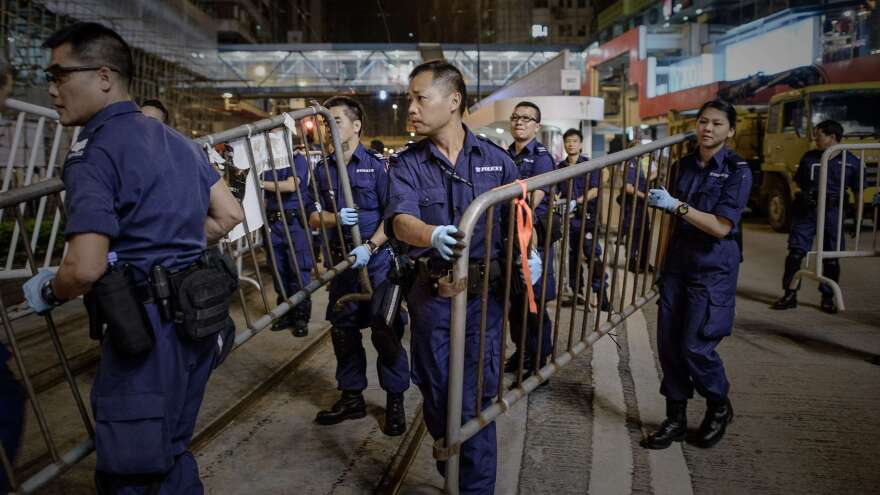 Police forces remove pro-democracy barricades in the Causeway Bay district of Hong Kong at dawn on Tuesday. Police armed with bolt cutters, chainsaws and sledgehammers made a renewed attempt to remove barricades along a stretch of the main protest site held by pro-democracy demonstrators for the past two weeks.