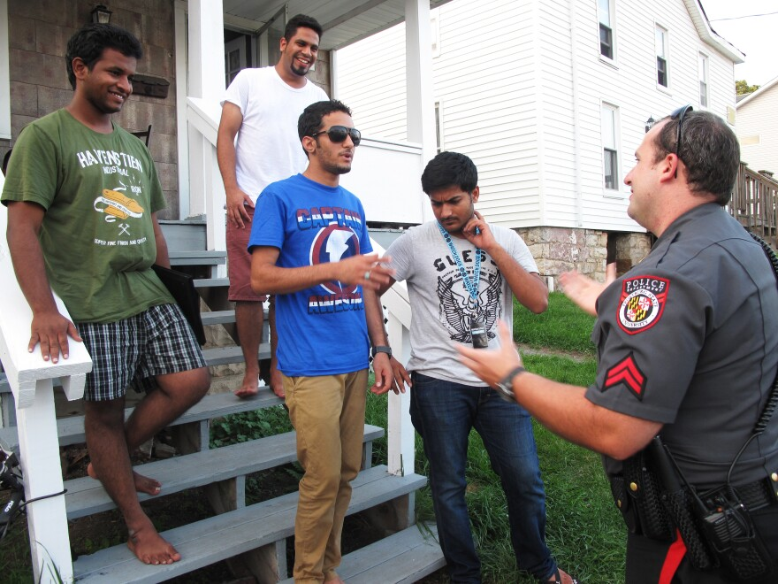"""Frostburg State University police officer Derrick Pirolozzi conducts a """"knock and talk"""" at a house near campus, reminding students of laws on underage drinking and open containers."""
