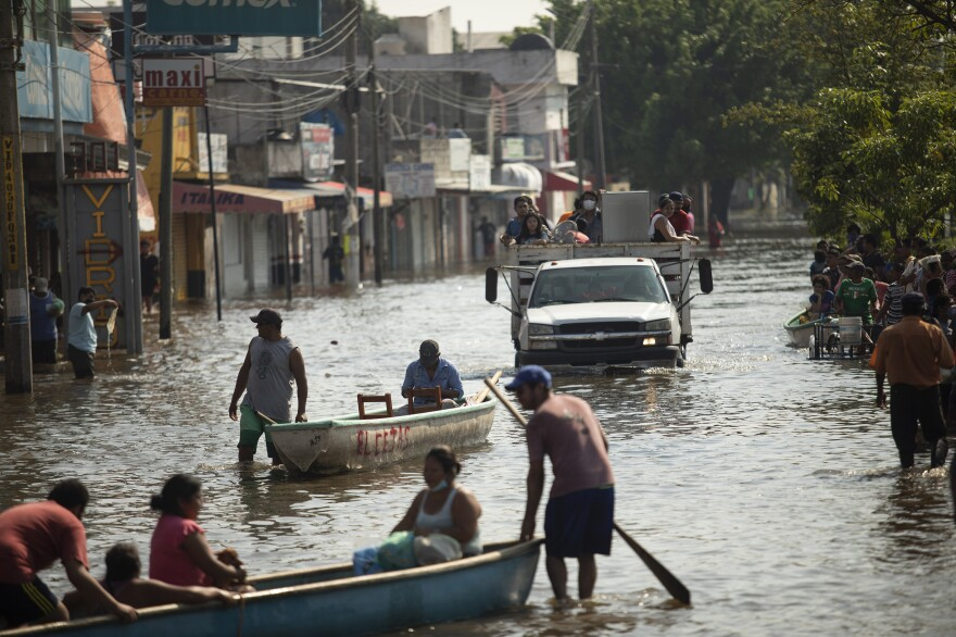Residents make their way through a flooded street in Villahermosa, Mexico, on Nov. 11, 2020. Rising seas contribute to more damaging floods from storms and tides.