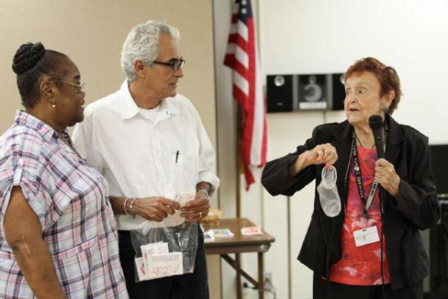 Marguerite Bryant, 69, (left) and program coordinator Victor DeSouza watch as Kate GeMeiner, 82, known as The Condom Lady, displays a female condom at a seminar.