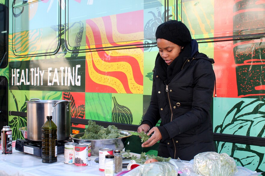 Danielle Cherry of Operation Food Search prepares citrus kale salad outside the public bus turned farmer's market parked in the JeffVanderLou neighborhood Sat. Dec. 19, 2015.