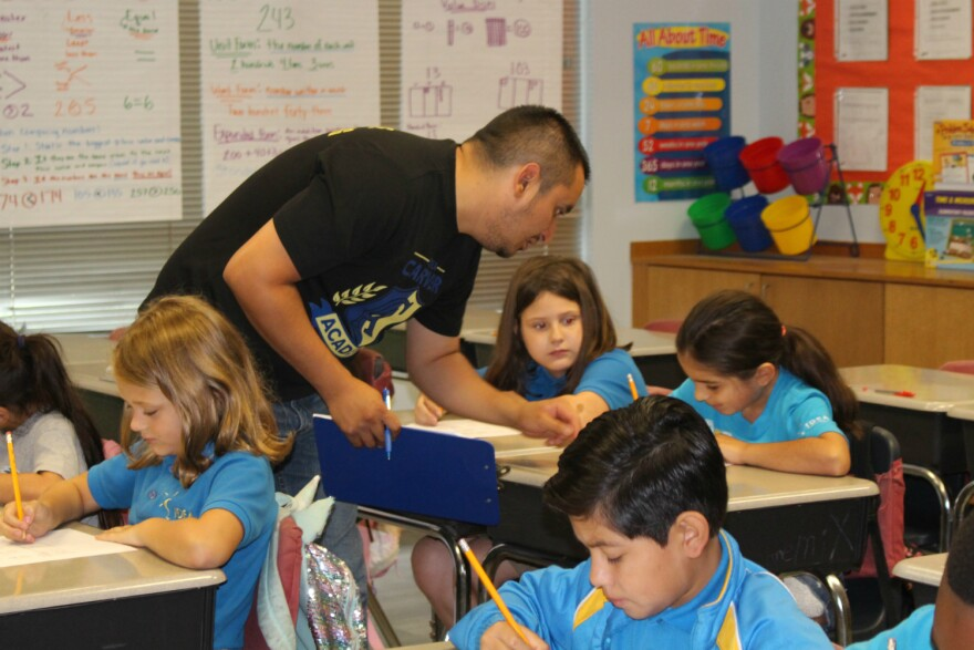 Second grade math teacher Armando Vela checks his students' work at IDEA Carver charter school on San Antonio's East Side May 24, 2019.