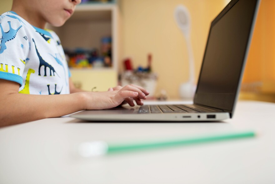 A child types on a laptop. (Getty Images)