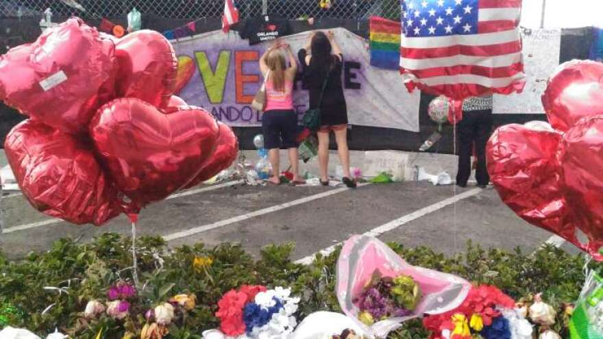 People write messages at the memorial outside the Pulse nightclub.