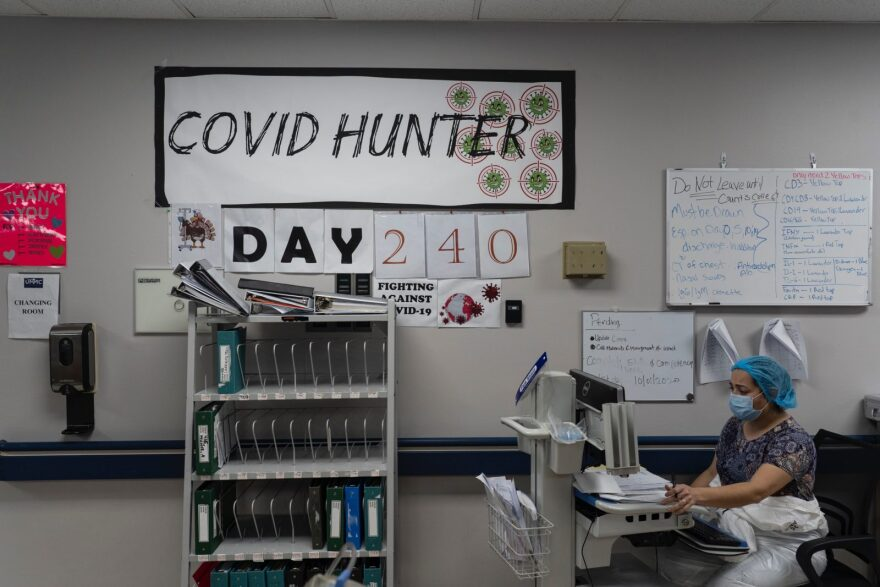 A medical staff member works on a computer as the number on the wall indicates the days since the hospital opened its COVID-19 unit at United Memorial Medical center in Houston, Texas.