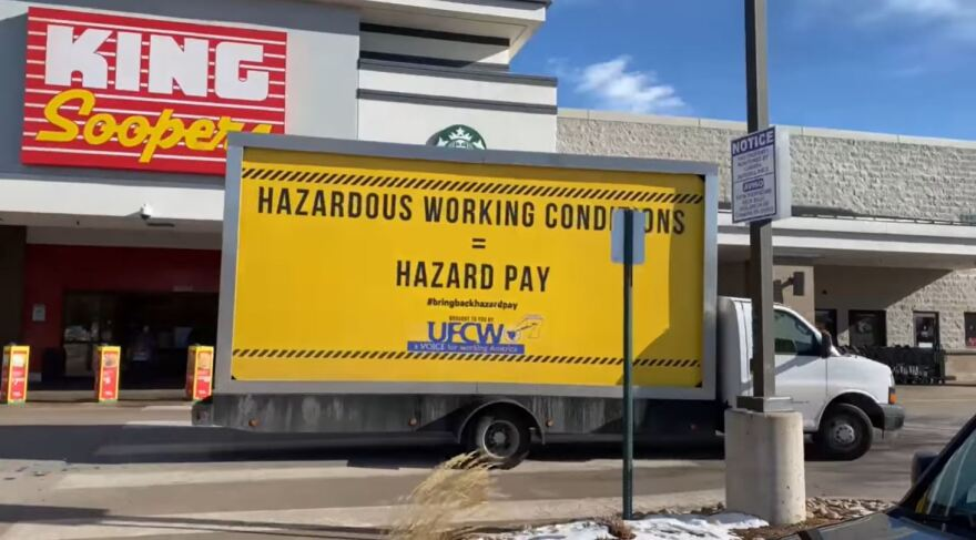 """A billboard truck with the words """"Hazardous Working Conditions = Hazard Pay"""" on a yellow background passes by a King Soopers."""