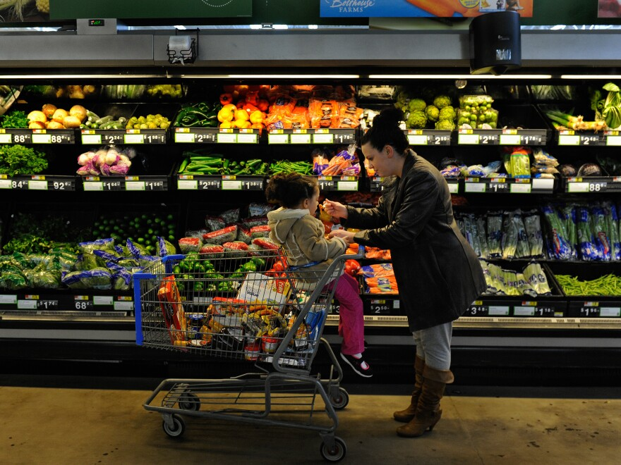 "Rebecka Ortiz offers her daughter a pasta sample at the store where she was using her food stamps to stock up on food for her family in Woonsocket, R.I. The Trump administration is proposing drastic changes in the ""food stamp"" program, now called SNAP. People getting that aid would lose much of their ability to choose the food they buy."