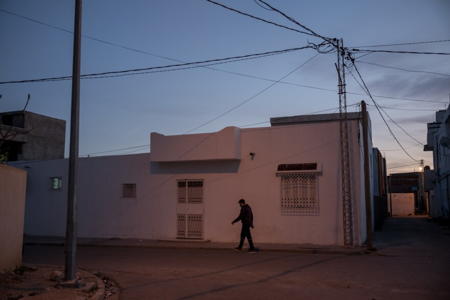 A man walks down a street in Jelma. Jelma is one example of the many interior towns of Tunisia suffering from high unemployment rates and overall lack of development.
